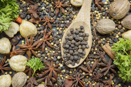 Top view of various herbs and spices with black peppercorn in the wooden spoon