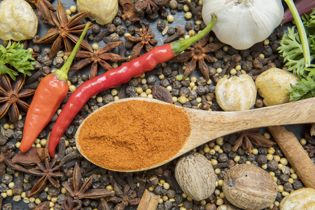 High angle view of various seasoning with turmeric powder in the wooden spoon
