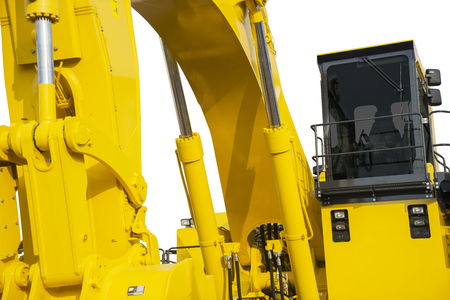 Closeup of hydraulic excavator with yellow color, isolated on white background Stock Photo