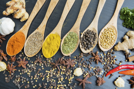 Top view of variety spices with row of wooden spoon on the table