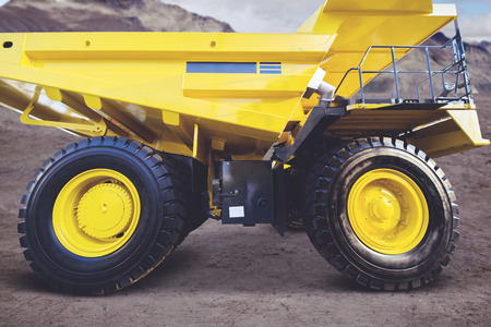 Side view of yellow mining truck parked in the construction site