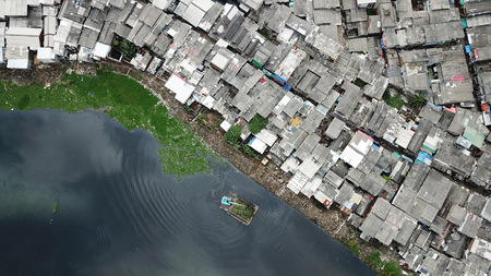 Top view of crowded slum neighborhood and an excavator on the lakeside at North Jakarta, Indonesia