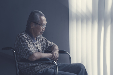 Lonesome senior man sitting on wheelchair near the window at nursing home