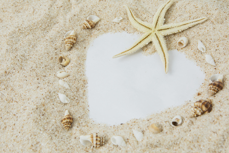 Top view of heart symbol with white beach sand, seashells, and starfish. Vacation concept