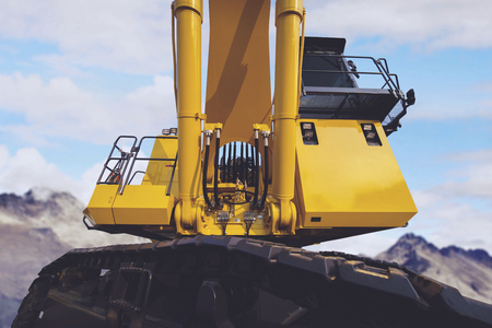 Low angle view of a big excavator at the construction site with blue sky background