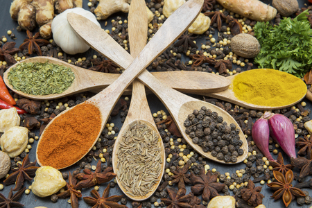 Top view of assorted herbs and spices in wooden spoons. Shot on the table