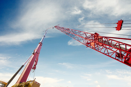 Low angle view of mobile crane and tower crane in construction site under blue sky