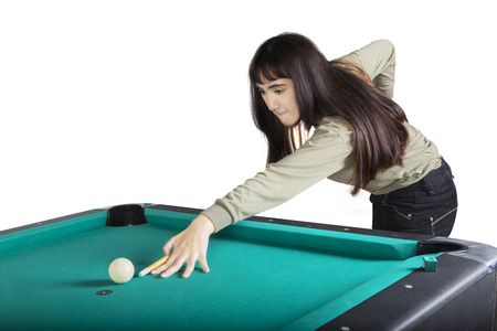 Pretty girl playing billiard and try to hit the ball, isolated on white background Archivio Fotografico