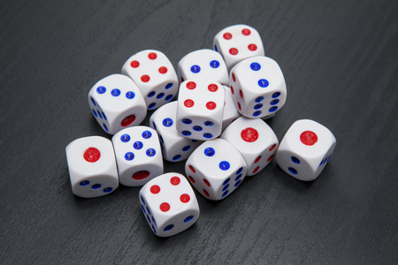 Top view of many white dices on the black wooden table