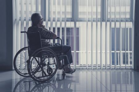 Einsamer alter Mann , der auf Rollstuhl sitzt , weil er ein Fenster nach ihm als Kinn für seine Freiheit und Freunde zieht Standard-Bild
