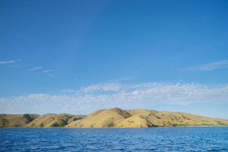 Beautiful landscape of Padar Island with savanna hills and blue water near Bali, Indonesia.