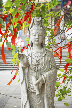 Picture of Kwan Im sculpture under a tree with red Chinese talisman in buddhist temple in Semarang, Indonesia
