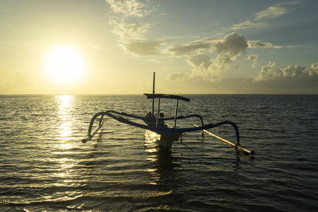 Image of beautiful sunrise with an empty fishing boat on the beach in Bali, Indonesia