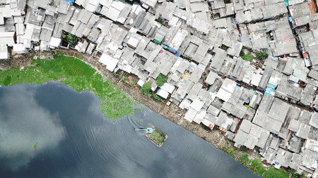 Top view of crowded houses at the slum neighborhood with an excavator on the lakeside at North Jakarta, Indonesia Stock Photo