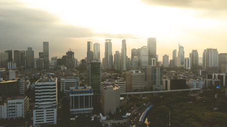 Aerial view of urban skyscrapers at sunset time in Jakarta, Indonesia