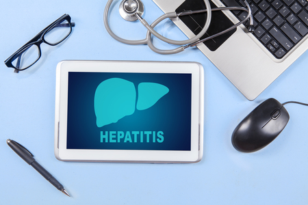 Top view of liver symbol and hepatitis word on the tablet screen with laptop and stethoscope on the table
