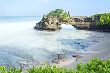 Beautiful Batu Bolong temple landscape under blue sky with frothy wave in Bali, Indonesia