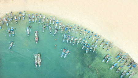Beautiful aerial view of traditional fisherman boats in a row on the Ujung Genteng beach with turquoise water, Sukabumi, West Java, Indonesia
