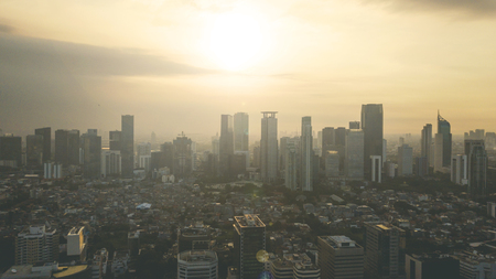 Bird view of beautiful sunset above skyscrapers and residential house in Jakarta, Indonesia