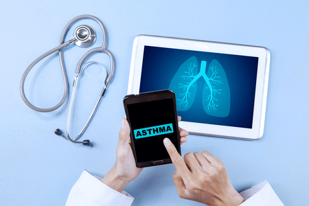 Top view of unknown male doctor hand pressing word of hepatitis on the smartphone screen with digital tablet and stethoscope on the table