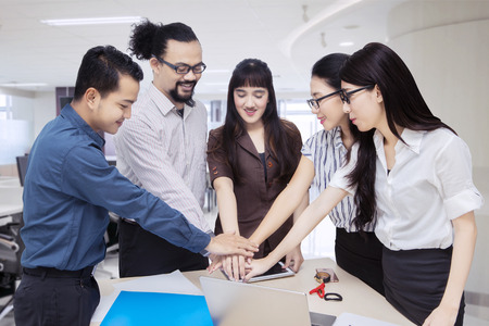 Image of diverse business people joining hands together for partnership in the office