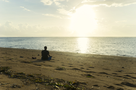Silhouette of an unknown man exercising yoga while sitting on the tropical beach