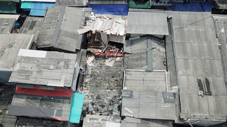 Aerial view of crowded slum house rooftop from a drone on the lakeside at North Jakarta, Indonesia