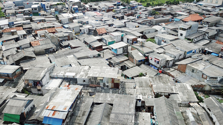 Aerial landscape of slum neighborhood with crowded rooftop of slum houses on the lakeside at North Jakarta, Indonesia