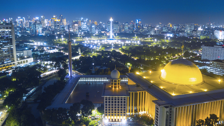 Beautiful Istiqlal mosque landscape with skyscrapers at night time in Jakarta, Indonesia