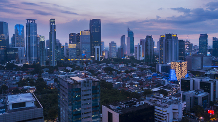 Aerial scenery of beautiful Jakarta city with skyscrapers and residential buildings at dusk