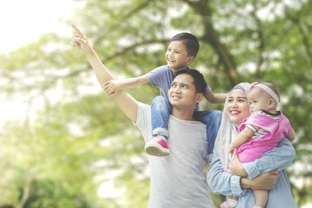 Imagen de familia musulmana mirando algo mientras están parados juntos en el parque Foto de archivo