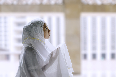 Young muslim woman praying in the mosque while wearing islamic clothes