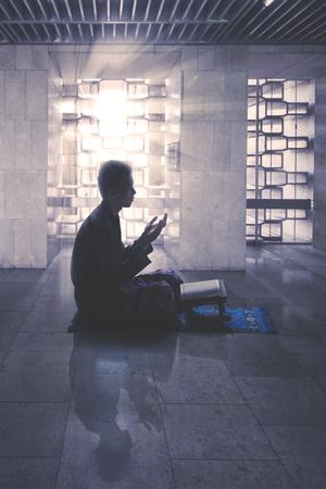 Silhouette d'homme musulman pieux priant Allah après avoir lu le Coran avec la lumière du soleil dans la mosquée Banque d'images