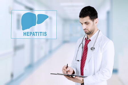 Picture of Arabian male physician writing on the clipboard while standing with virtual of liver symbol and hepatitis word. Shot in the hospital Reklamní fotografie