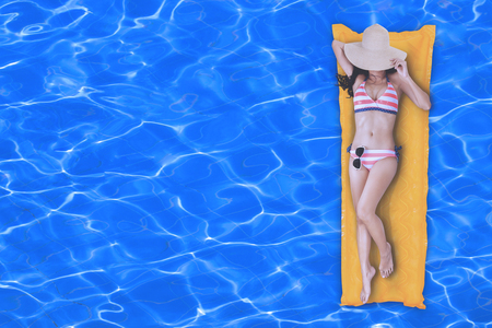 Top view of slim young woman in bikini enjoying the day on the yellow air mattress in swimming pool with copy space
