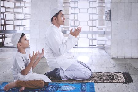 モスクでサラトをした後、一緒に祈る彼の父親と小さな男の子のサイドビュー
