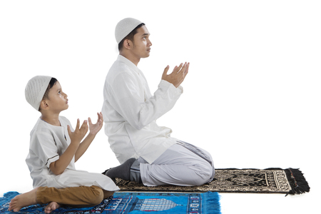 Side view of young father with his son praying together after doing Salat, isolated on white background