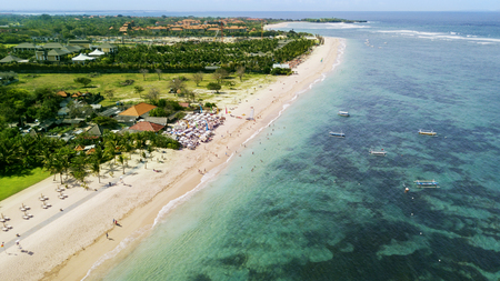 Aerial view of crowded tourists enjoying a holiday at Nusa Dua beach in Bali, Indonesia