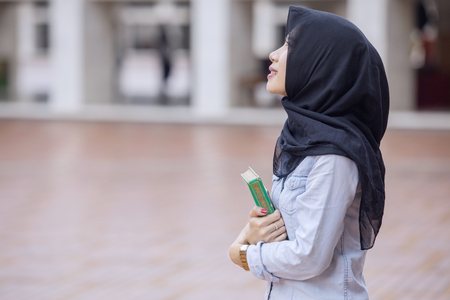 Pretty girl wearing a veil while carrying a Quran and standing in the Istiqlal mosque