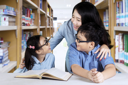 Photo of two elementary students talking with their teacher while studying together in the library