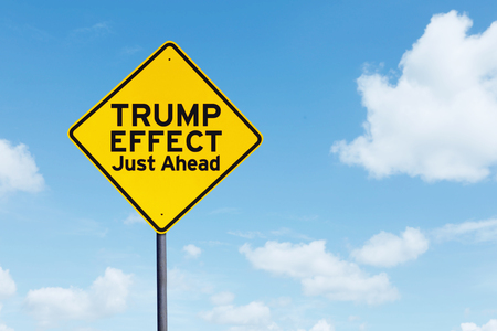 Picture of yellow signpost with text of Trump Effect Just ahead under blue sky
