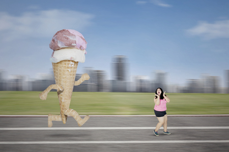 Diet concept. Young fat woman chased by an ice cream while running on the track with scared expression