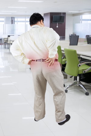 Back view of obese businessman having backache while standing in the office