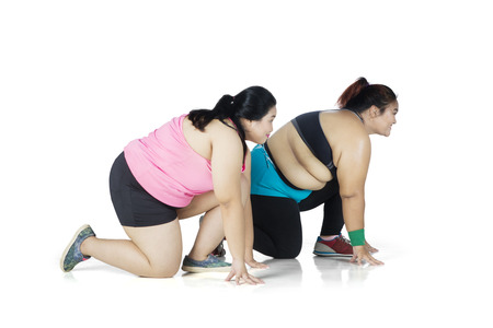 Side view of two overweight women ready to run while kneeling together, isolated on white background
