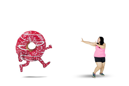 Diet concept. Fat woman chased by tasty donut while running in the studio, isolated on white background Stock Photo