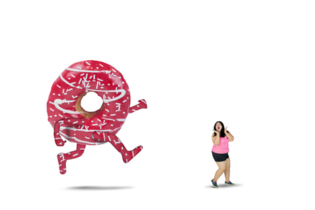 Picture of young fat woman chased by a big pizza with scared expression, isolated on white background