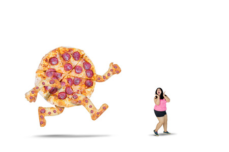 Picture of young overweight woman chased by a big pizza with scared expression, isolated on white background