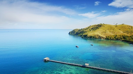 Aerial view of wooden pier with turquoise water in Flores island near Bali, Indonesia Stock Photo