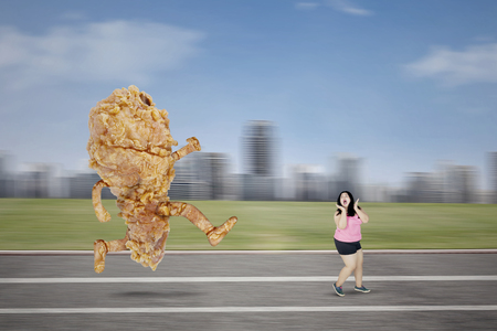 Picture of Asian obese woman chased by a fried chicken while running on the track