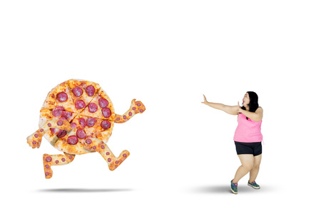 Young fat woman looks fearfully while running away from a pizza, isolated on white background